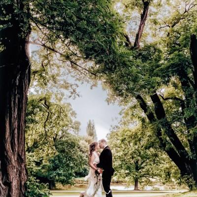 Hochzeitspaar steht sich gegenüber in malerischer Kulisse eingerahmt von Bäumen sie küssen sich und die Braut lässt einen Fuß flippen und hebt ihn nach hinten weg in die Luft