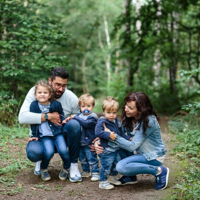 Frau und Mann mit zwei kleinen Jungs und einem Mädchen hocken auf einem Waldweg